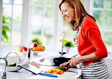 Woman In Kitchen Following Recipe On Digital Tablet